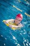 Jeune fille apprenant à nager dans la piscine avec le panneau de mousse Images libres de droits