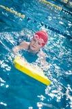 Jeune fille apprenant à nager dans la piscine avec le panneau de mousse Photos libres de droits