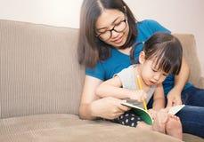 Jeune fille apprenant comment écrire avec sa mère Photo libre de droits