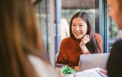 Jeune fille asiatique amis causant et à l'aide de l'ordinateur portable en café au café de café à l'université parlant et riant e photo stock
