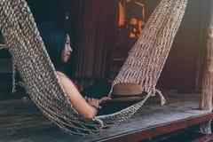 Jeune fille asiatique caucasienne balançant dans un hamac dans une paresse agréable d'une soirée de week-end photographie stock libre de droits