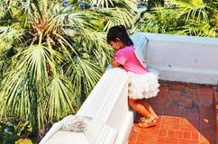 Jeune fille asiatique pensant comme elle regarde fixement au-dessus d'un mur Image stock
