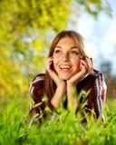 Jeune fille assez joyeuse se trouvant sur l'herbe verte Photos stock