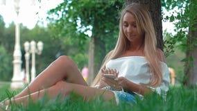 Jeune fille attirante à l'aide du smartphone tout en se reposant dans le parc, effets de fusée banque de vidéos