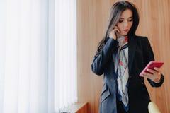 Jeune fille attirante émotive dans des vêtements de style des affaires à une fenêtre avec un téléphone dans un bureau ou un amphi photo stock