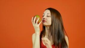 Jeune fille attirante avec de longs cheveux foncés jugeant la mangue Jaunâtre-rouge disponible et essayant de manger de ce fruit  banque de vidéos