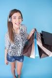 Jeune fille attirante avec des paquets et des écouteurs Photographie stock