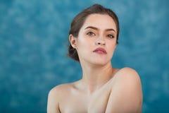 Jeune fille attirante avec les cheveux noirs fixes derrière, les grands yeux, les sourcils épais et les épaules nues tenant la ma Photo stock