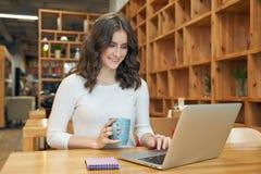 Jeune fille attirante d'étudiant faisant le travail se reposant à une table Photo stock