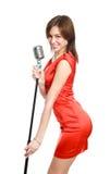 Jeune fille attirante dans une robe rouge avec le microphone Photographie stock libre de droits