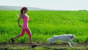 Jeune fille attirante de sport courant avec le chien en parc Photos stock