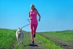 Jeune fille attirante de sport courant avec le chien en parc Photos libres de droits