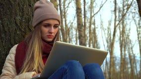 Jeune fille attirante en parc d'automne sous un arbre, se reposant au sol, fonctionnant dans un ordinateur portable Fin vers le h banque de vidéos