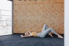 Jeune fille attirante faisant des exercices de forme physique avec du yoga sur le plancher sur un fond en bois photo stock