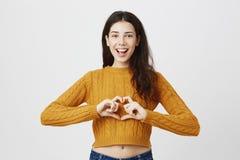 Jeune fille attirante montrant le geste de coeur tout en souriant largement et regardant fixement l'appareil-photo, le chandail c Images stock