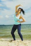 Jeune fille attirante pratiquant des exercices physiques sur une plage pendant l'été Images libres de droits