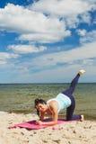 Jeune fille attirante pratiquant des exercices physiques sur une plage pendant l'été Photographie stock libre de droits