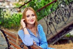 Jeune fille attirante se reposant en parc de ville images stock
