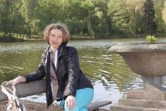 Jeune fille attirante sur un banc par le lac Image libre de droits