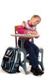 Jeune fille au bureau à l'école sur le blanc photographie stock