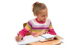 Jeune fille au bureau à l'école sur le blanc Photographie stock libre de droits