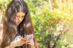 Jeune fille aux cheveux longs à l'aide du téléphone dans le parc de ville sur une somme Photo stock