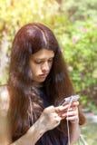 Jeune fille aux cheveux longs à l'aide du téléphone dans le parc de ville sur une somme Photos stock
