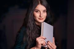 Jeune fille aux cheveux longs de brune avec un livre regardant la caméra photos libres de droits