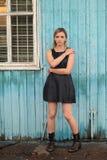 Jeune fille aux yeux bruns blonde dans la robe et le St en cuir noirs de bottes Image stock