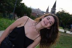 Jeune fille avec de longs cheveux bruns, dans le dessus de réservoir noir tout en regardant l'appareil-photo souriant à Vérone, l photo stock