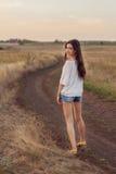 Jeune fille avec de longs cheveux bruns marchant loin sur la route images libres de droits