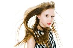 Jeune fille avec de longs poils droits soufflés par le vent dans le studio photographie stock libre de droits