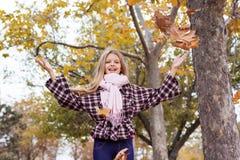 Jeune fille avec des feuilles de vol en parc d'automne images stock