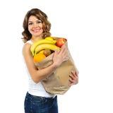 Jeune fille avec des fruits dans le sac de papier d'isolement sur le blanc Photo libre de droits