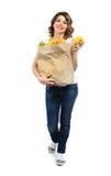 Jeune fille avec des fruits dans le sac de papier d'isolement sur le blanc Images stock