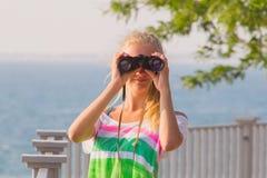 Jeune fille avec des jumelles à disposition Photo libre de droits