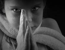 Jeune fille avec des mains dans la prière Images stock