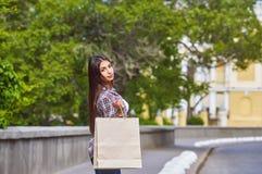 Jeune fille avec des paniers après l'achat dans la ville Photographie stock libre de droits