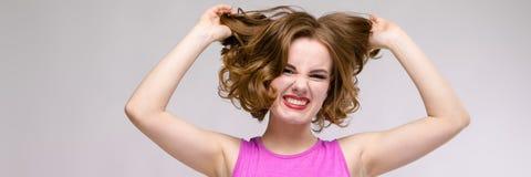 Jeune fille avec du charme dans la robe rose sur le fond gris Une jeune fille tient ses cheveux dans des ses mains photographie stock