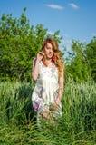 Jeune fille avec du charme dans un bain de soleil blanc beau, marche sexy dans le domaine parmi les épillets de blé avec les pavo Photo libre de droits