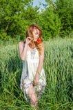Jeune fille avec du charme dans un bain de soleil blanc beau, marche sexy dans le domaine parmi les épillets de blé avec les pavo Images libres de droits