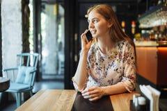 Jeune fille avec du charme parlant au téléphone seul se reposant dans le café dans son temps disponible, femme attirante avec un  photos stock