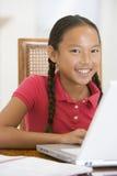Jeune fille avec l'ordinateur portatif dans la salle à manger image libre de droits