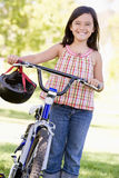 Jeune fille avec la bicyclette souriant à l'extérieur Images libres de droits