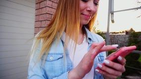 Jeune fille avec la fin dactylographiant des mains par le smartphone tenant le garage proche clips vidéos