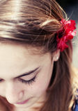 Jeune fille avec la fleur rouge sur son cheveu Photos stock