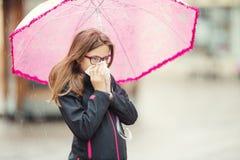 Jeune fille avec la grippe soufflant son nez avec un papier de soie de soie sous la pluie de ressort Photos stock