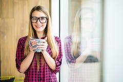 Jeune fille avec la tasse de café avec bonne humeur pendant le matin dans le bureau moderne près de la fenêtre photographie stock