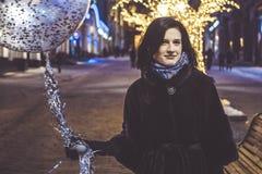 Jeune fille avec le baloon marchant dans les rues de ville de nuit Image stock