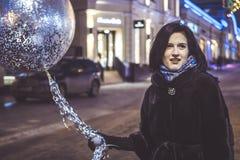 Jeune fille avec le baloon marchant dans les rues de ville de nuit Photographie stock libre de droits